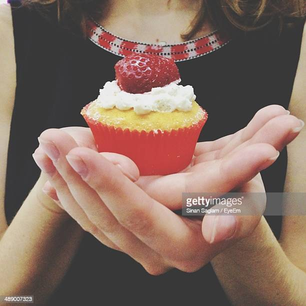 Midsection of woman holding strawberry cupcake