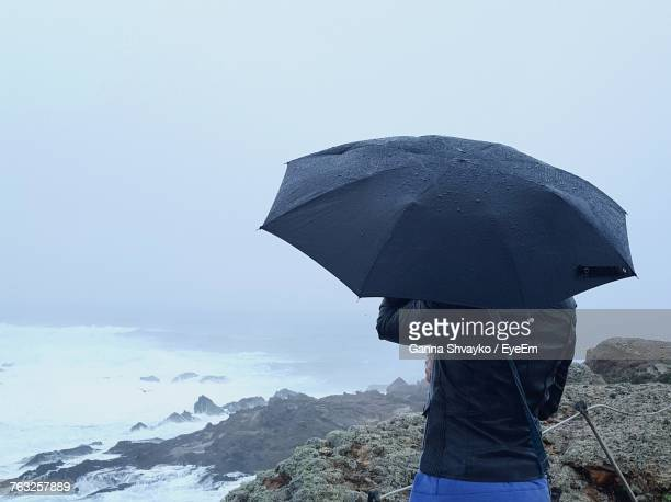 Midsection Of Woman Holding Umbrella On Cliff During Rain