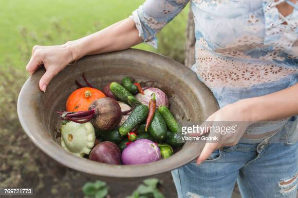 Midsection of woman holding vegetables in container