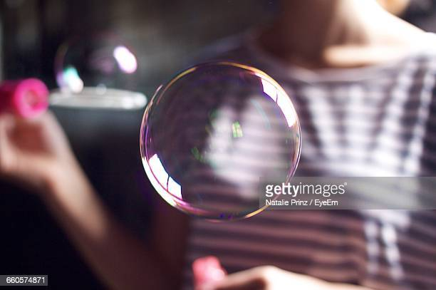 Midsection Of Woman Holding Wand With Bubble
