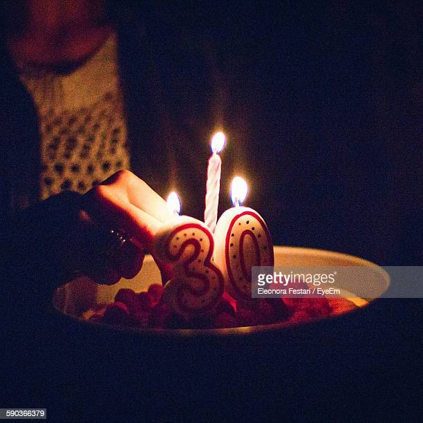Midsection Of Woman Lighting Birthday Candles In Darkroom