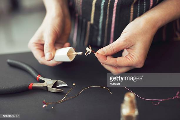 Midsection of woman making wire flower at table