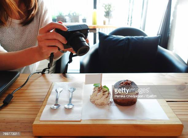 Midsection Of Woman Photographing Food On Table