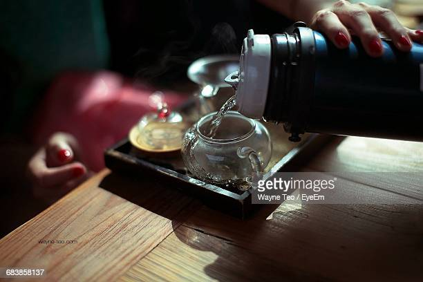 Midsection Of Woman Pouring Water In Tea Cup On Table