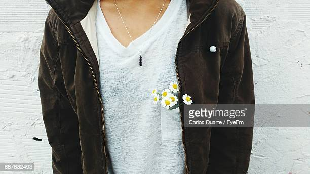 Midsection Of Woman Standing With White Daisy Flowers In Pocket