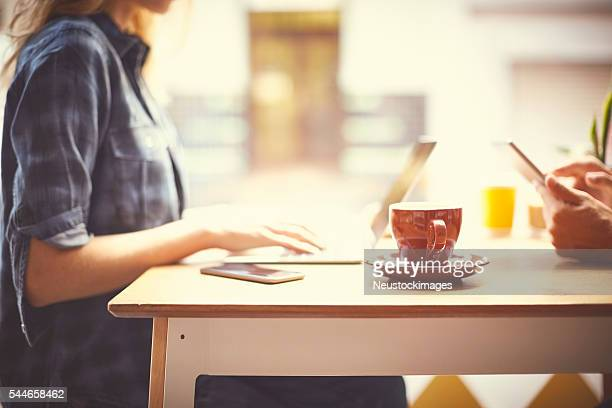 Midsection of woman using laptop at table in cafe