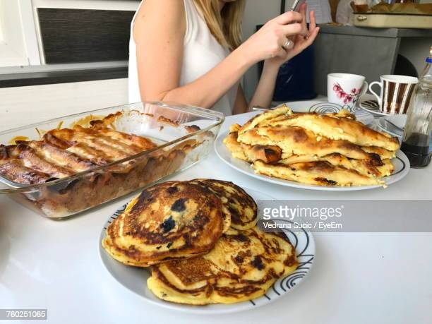 Midsection Of Woman Using Phone While Having Pancakes On Table