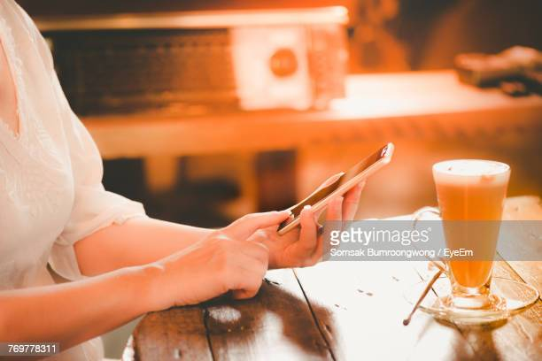 Midsection Of Woman Using Smart Phone While Sitting By Coffee On Restaurant Table