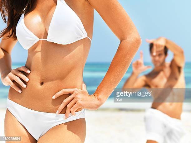 Midsection of woman wearing a bikini on the beach