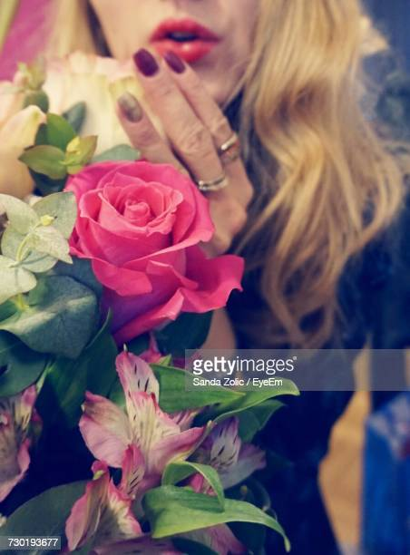 Midsection Of Woman With Blond Hair By Roses