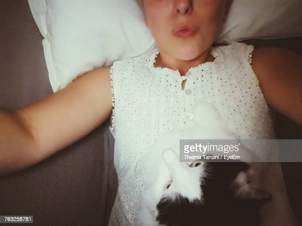 Midsection Of Woman With Cat Lying On Bed At Home