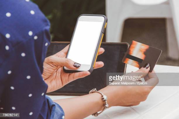 Midsection Of Woman With Credit Card Using Mobile Phone