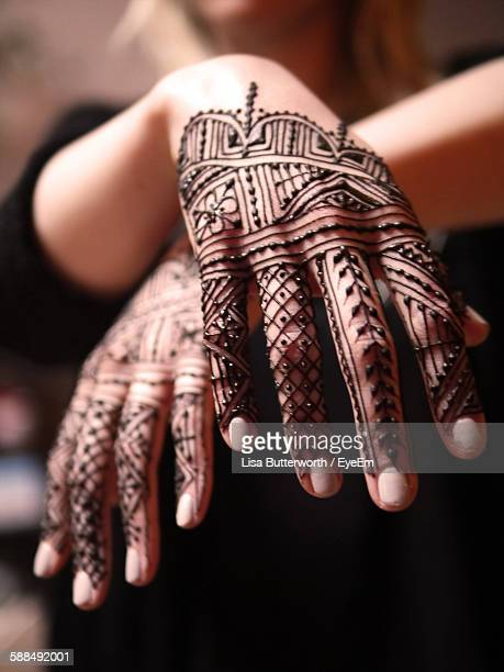 Midsection Of Woman With Henna Tattoos On Hands