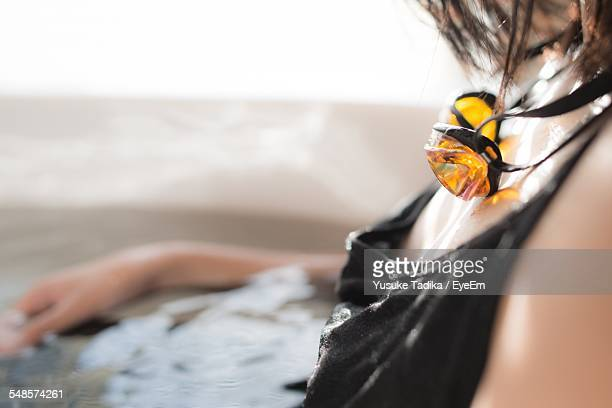 Midsection Of Woman With Swimming Goggles In Bathroom