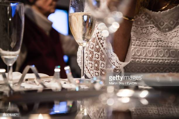 Midsection Of Woman With Wine On Table