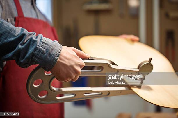 Midsection of worker using tool to make guitar