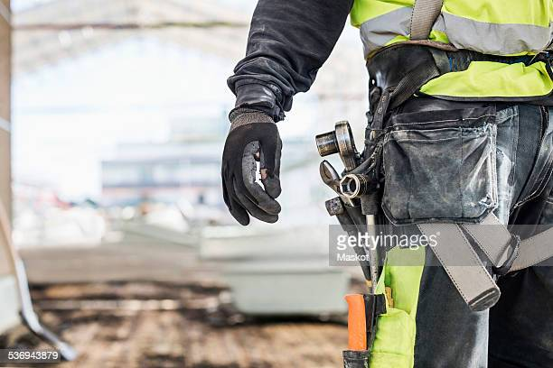 Midsection of worker wearing tool belt at construction site