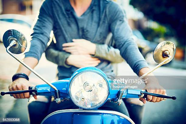 Midsection of young couple riding motor retro scooter