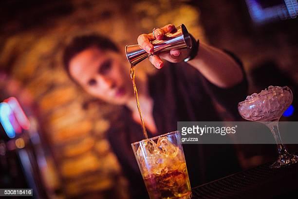 Partie médiane de jeune femme barman de vous préparer un cocktail dans notre bar à cocktails