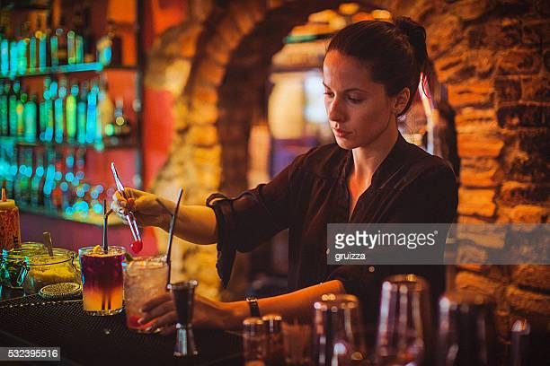Partie médiane de jeune femme barman préparer des cocktails au bar à cocktails
