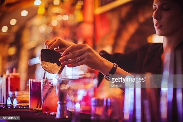 Bauchgegend von junge weibliche Barkeeper bereiten Cocktails in der cocktail-bar
