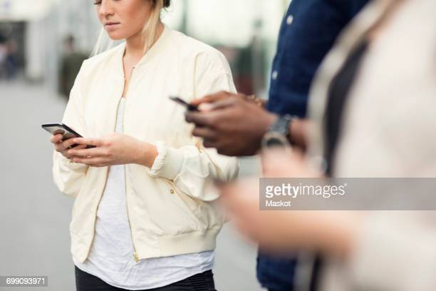 Midsection of young friends using smart phones in city