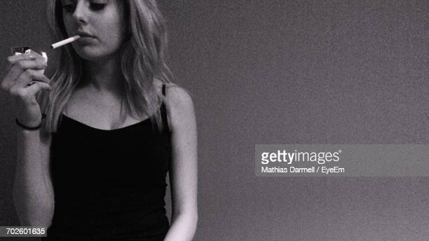 Midsection Of Young Woman Smoking Cigarette While Standing Against Wall