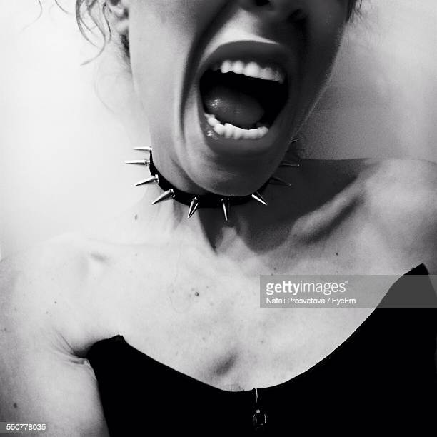 Midsection Of Young Woman Wearing Spiked Choker With Mouth Open Against White Background