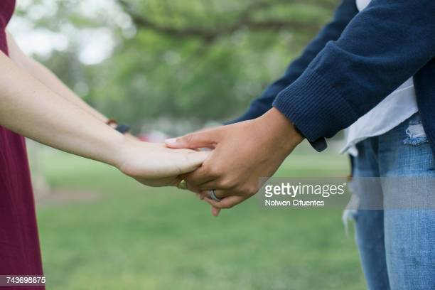 Midsection of young women holding hands at park