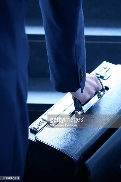 Midsection view of businessman carrying suitcase