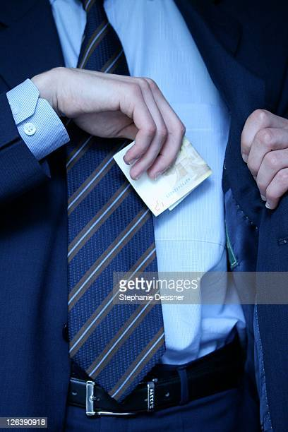 Midsection view of businessman putting banknote in his shirt's pocket