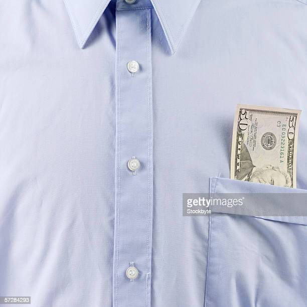 Mid-section view of businessman with dollar bill in his shirt pocket