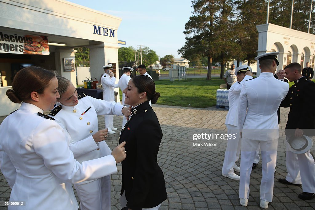 Midshipmen 1st Class Mackinzie Spaich (C), has class mates help her with last minute uniform adjustments before graduation ceremonies at the U.S. Naval Academy May 27, 2016 in Annapolis, Maryland. This is the first year that female Midshipmen will be wearing the same uniform as the male Midshipmen. U.S. Secretary of Defense Ashton Carter is this year's commencement speaker.