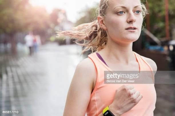 Midshot of female runner running in urban area in city.