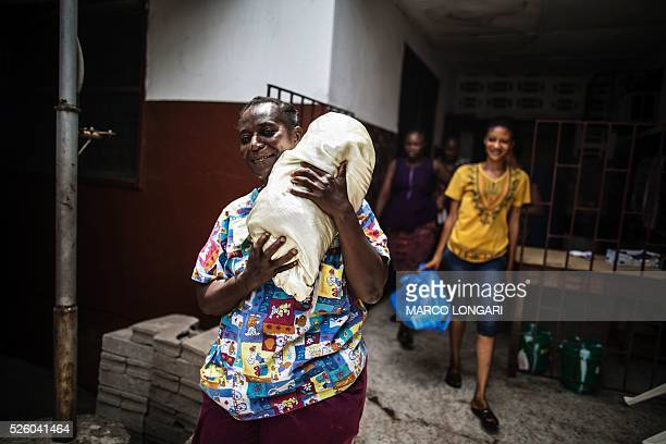 A midwife carries a newborn outside the premises escorted by the extended family of the child at the Star of the Sun Health Centre in the Monrovia...