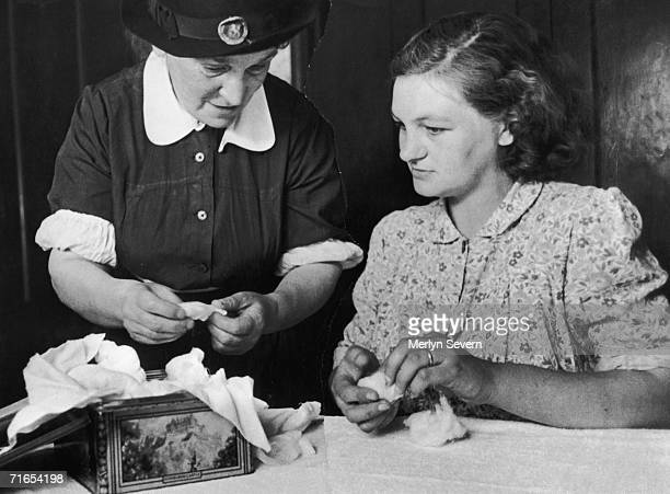 A midwife helps an expectant mother to pack a biscuit tin with gauze and cotton wool after which it will be sterilised in the oven in preparation for...