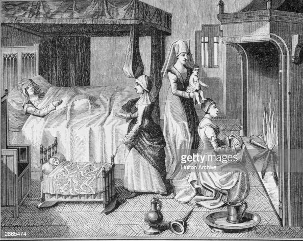 Midwives tend to a newborn baby while the exhausted mother rests in bed circa 1450 Another child lies in a cradle beside her being rocked by a...