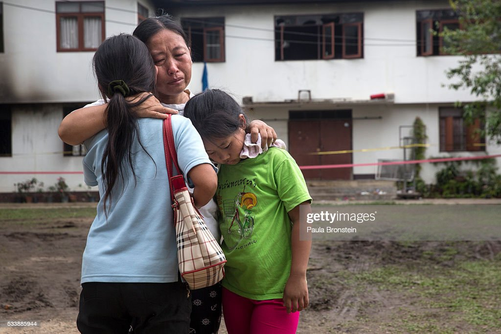 Mie Pandan (C) and her daughter Chitlada,10, (R) embrace another relative outside of the school dormitory where a fire broke out on Sunday night killing at least 17 girls on May 24, 2016 in Wiang Papao, Chiang Rai province, Thailand. The Pitakkiat Wittaya school was home to pupils from impoverished local hill tribes in the region, they were aged between 5 to 13. Based on reports, many of the 38 students were asleep when the fire swept through the elementary school in Chiang Rai Province and investigations are still being carried out to find the cause of the fire.
