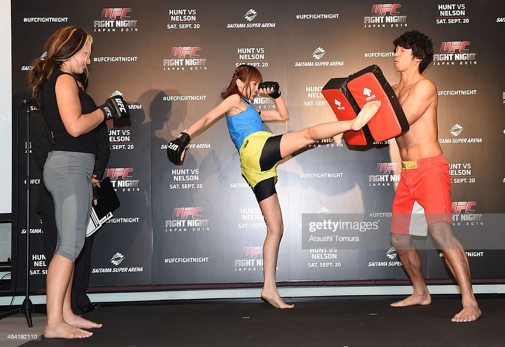 Miesha Tate, UFC women's bantamweight teaches Minami Akina and Japanese comedianTomoharu Shoji how to kick to during a UFC press conference at Akasaka Garden City on August 26, 2014 in Tokyo, Japan.