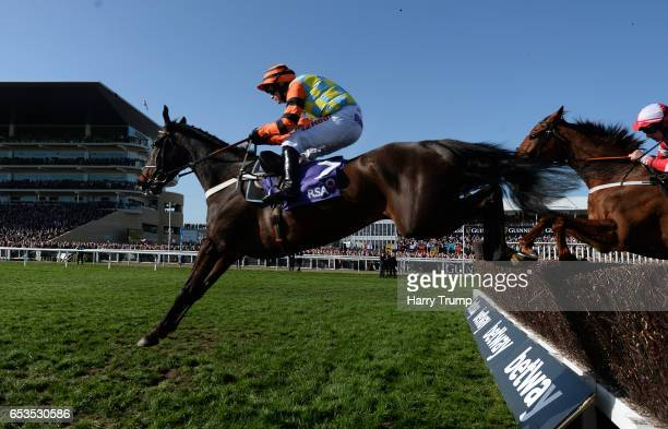 Might Bite ridden by Nico De Boinville jump on their way to winning the RSA Novices Steeple Chase during Ladies Day of the Cheltenham Festival at...
