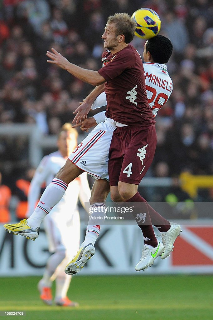 Migjen Basha (L) of Torino FC goes up with Urby Emanuelson of AC Milan during the Serie A match between Torino FC and AC Milan at Stadio Olimpico di Torino on December 9, 2012 in Turin, Italy.