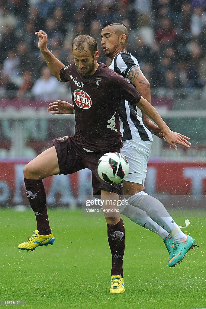 Migjen Basha (L) of Torino FC is challenged by Arturo Vidal of Juventus during the Serie A match between Torino FC and Juventus at Stadio Olimpico di Torino on April 28, 2013 in Turin, Italy.