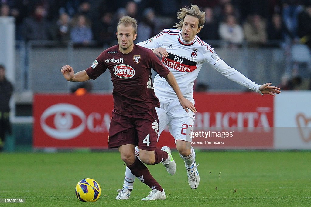 Migjen Basha (L) of Torino FC is challenged by Massimo Ambrosini of AC Milan during the Serie A match between Torino FC and AC Milan at Stadio Olimpico di Torino on December 9, 2012 in Turin, Italy.