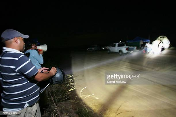 Migrant activists protesting nightly patrols by citizen volunteers who search for people crossing USMexico border use powerful spot lights and loud...