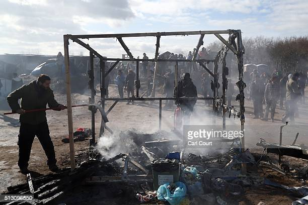 A migrant and activist douse the flames of what remains of a hut as part of the 'jungle' migrant camp is cleared on February 29 2016 in Calais France...