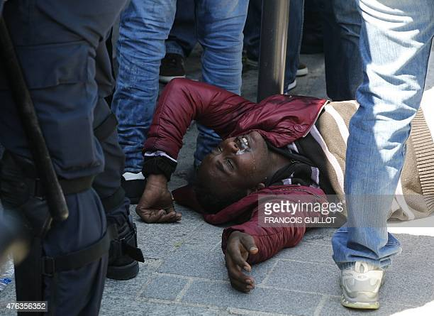 A migrant arrested by the police lies on the ground on June 8 2015 in front of the Vaclav Havel library rue Pajol in the 18th arrondissement of Paris...
