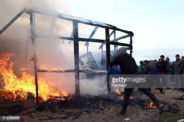 A migrant attempts to extinguish a fire as a hut burns as police officers clear part of the 'jungle' migrant camp on February 29 2016 in Calais...