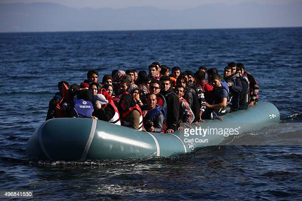 A migrant boat arrives after making the crossing from Turkey to the Greek island of Lesbos on November 12 2015 in Sikaminias Greece Rafts and boats...