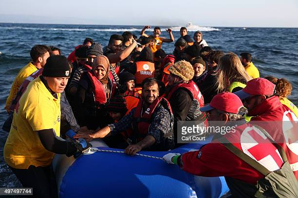 A migrant boat is pulled ashore by aid workers after making the crossing from Turkey to the Greek island of Lesbos on November 17 2015 in Sikaminias...