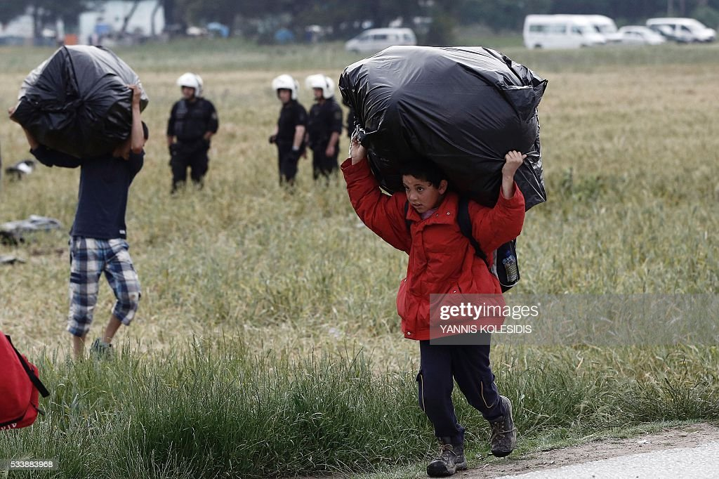 A migrant boy carries his belongings during an evacuation operation by police forces of a makeshift migrant camp at the border at the Greek-Macedonian border near the village of Idomeni, on May 24, 2016. In an operation which began shortly after sunrise on May 24, hundreds of Greek police began evacuating the sprawling camp which is currently home to 8,400 refugees and migrants, among them many families with children, an AFP correspondent said. At its height, there were more than 12,000 people crammed into the site, many of them fleeing war, persecution and poverty in the Middle East and Asia, with the camp exploding in size since Balkan states began closing their borders in mid February in a bid to stem the human tide seeking passage to northern Europe. / AFP / POOL / YANNIS